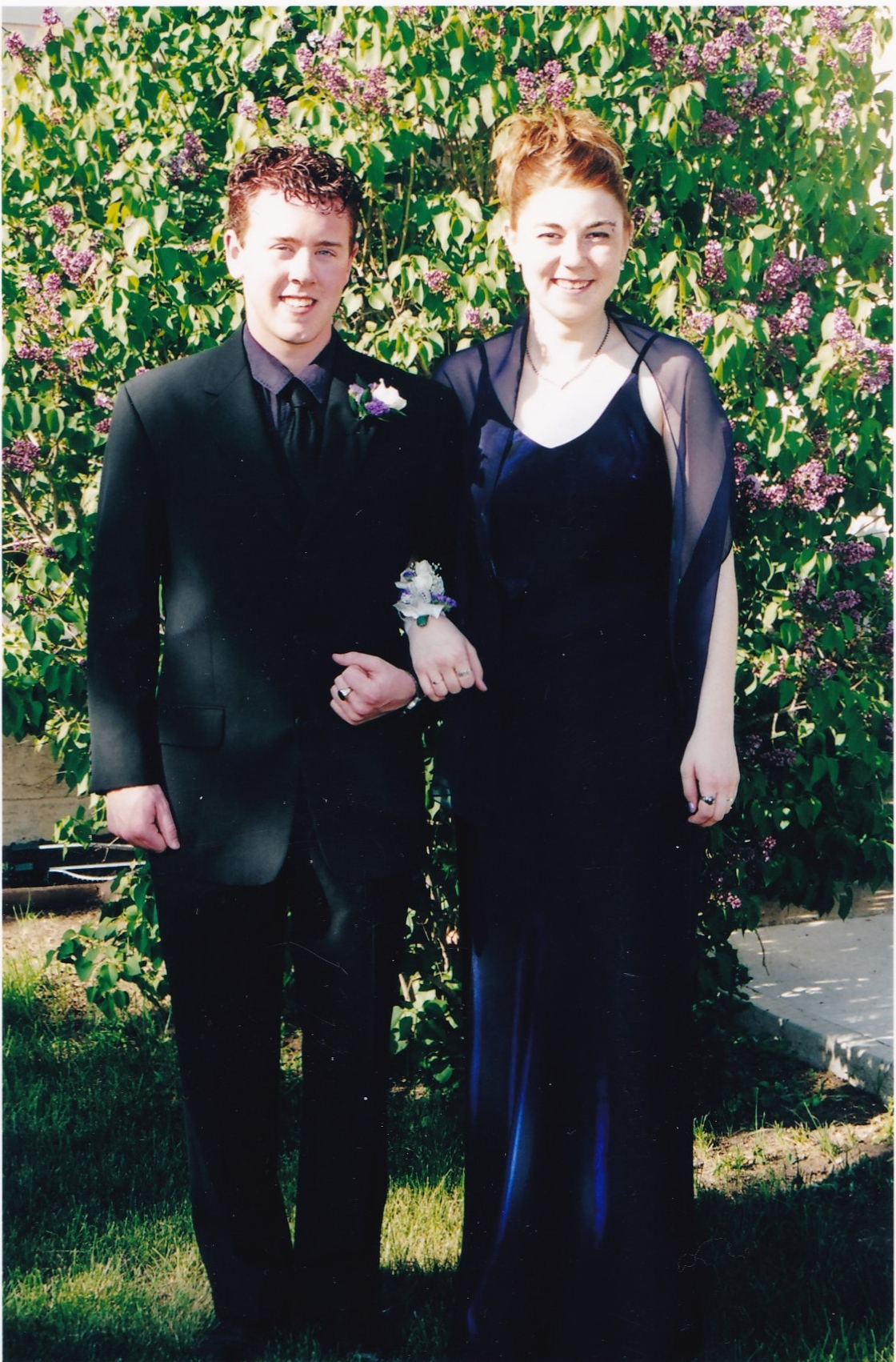 Graduation photographer a full length photoo f my date and I standing in front of a purple lilac bush. Our faces are in the sun and our bodies are in shadow which resulted in overexposure to our faces and underexposure to our bodies making my dress look black