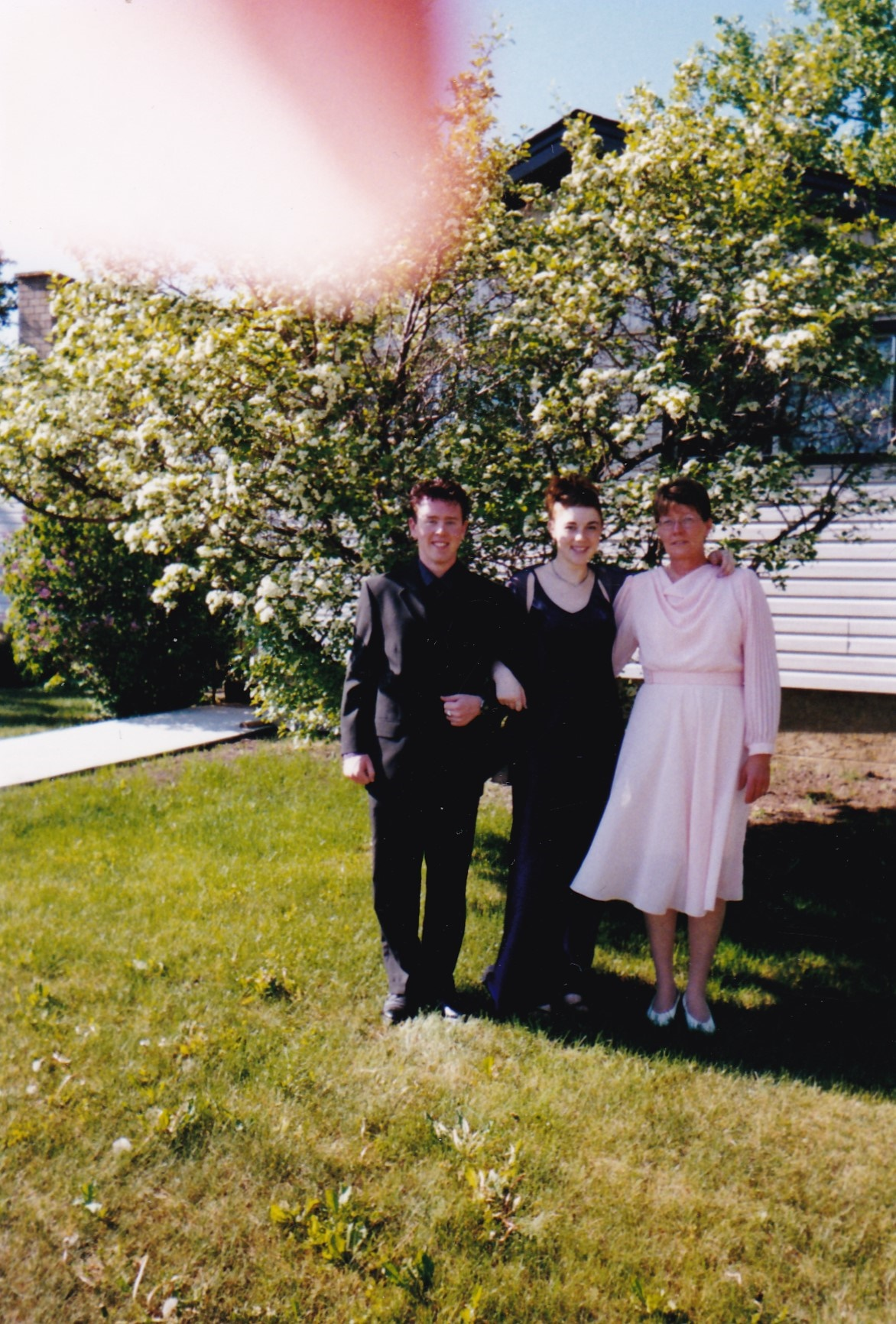 Graduation photographer a photo of me, my date, and my mom standing in front of a white lilac tree. There is a fingertip in the upper corner of the photo. My dress which is purple actually looks black