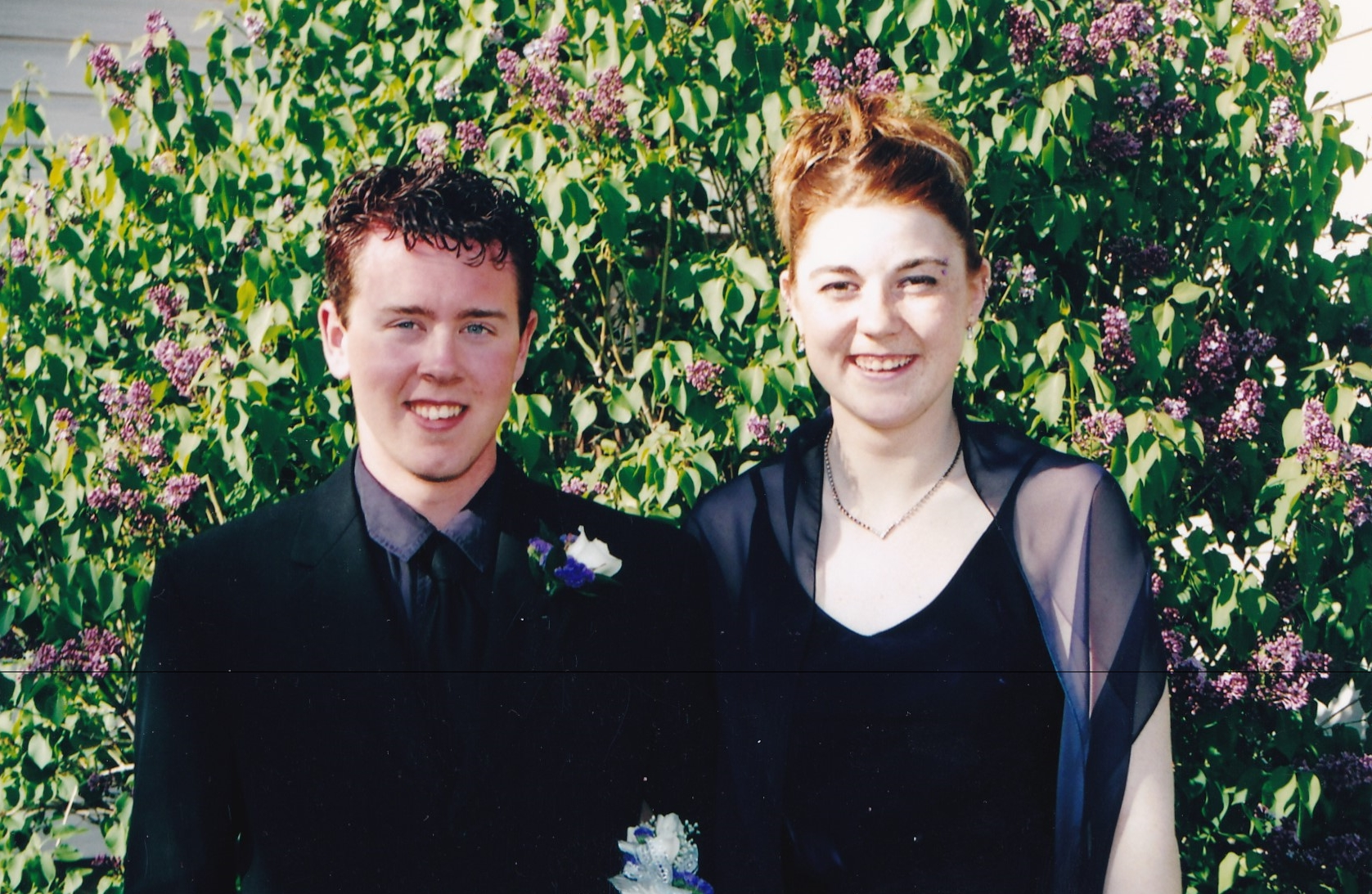 Graduation photographer a waist up shot of me and my date on prom day. Purple was our color but the purple is lost in the difficult exposure