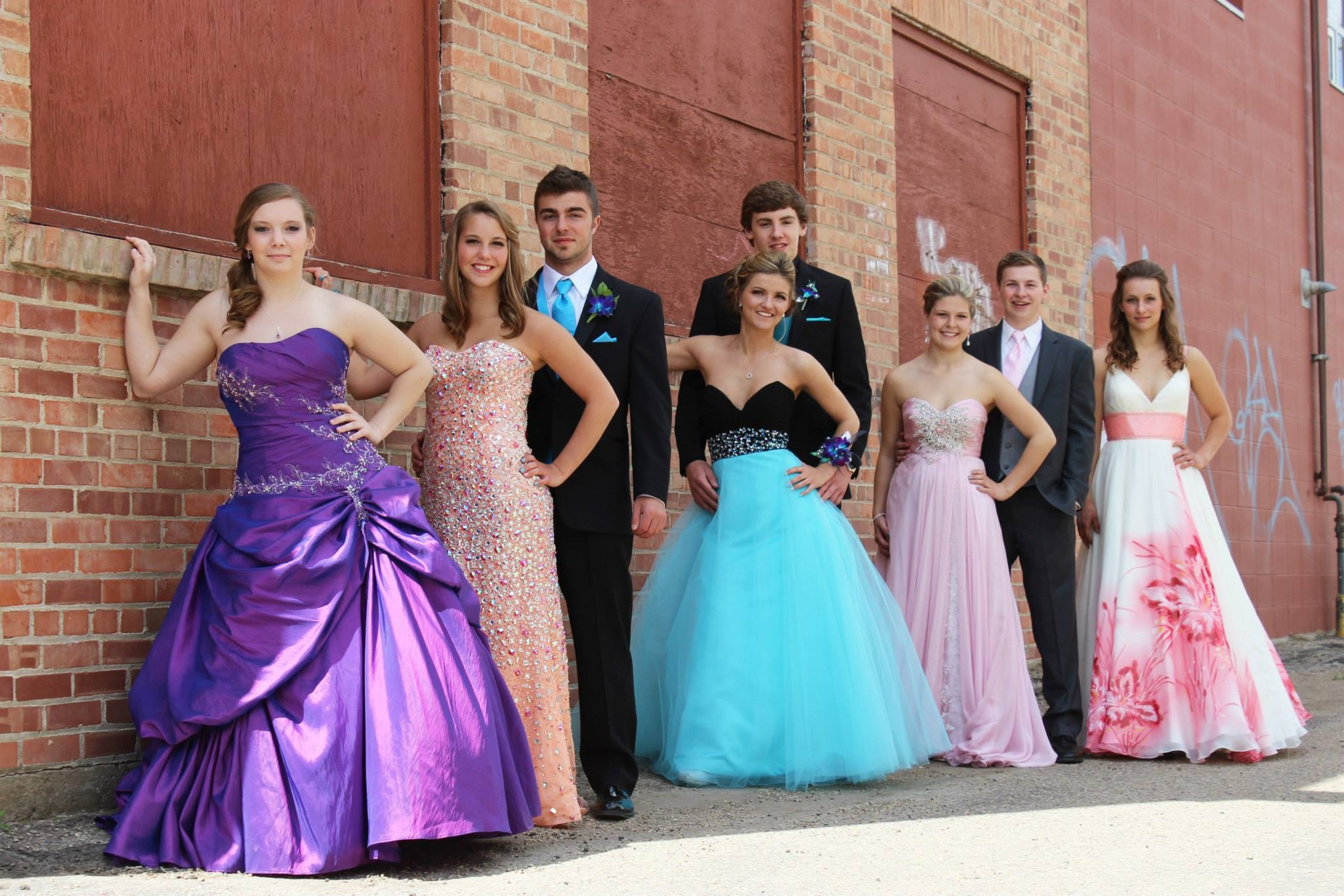 Prom Photographer A group of female and male graduates stand posed in a line against a brick wall, smiling at the camera