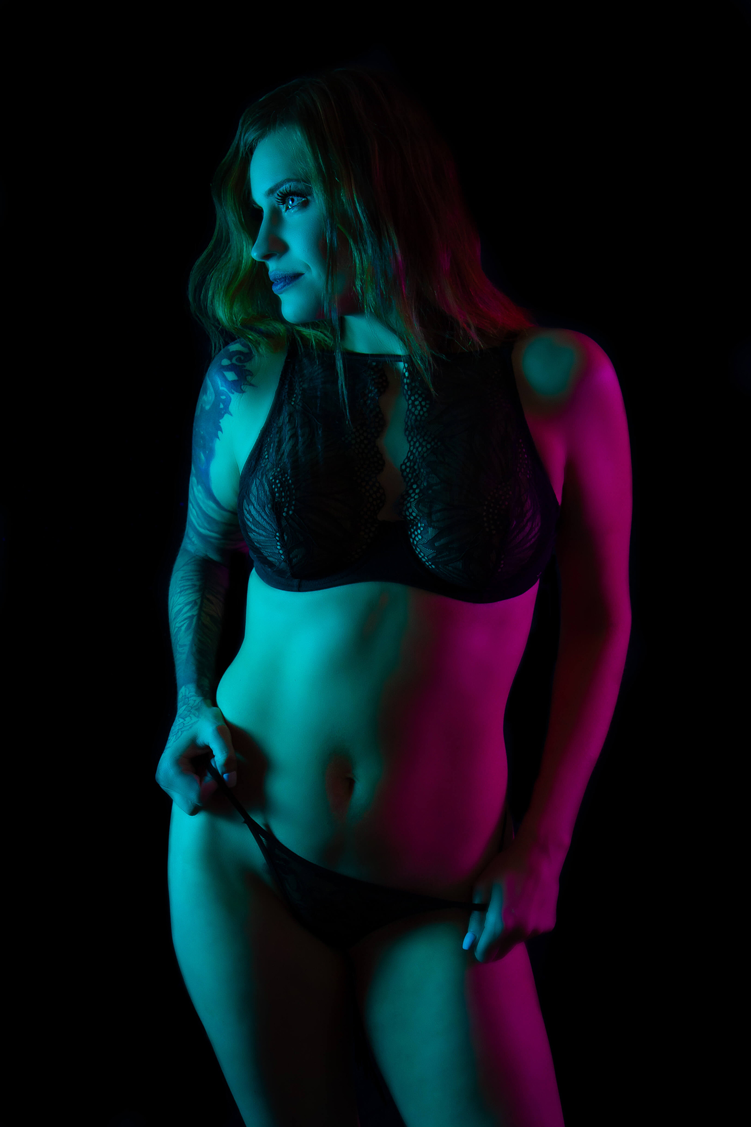 Saskatoon boudoir a woman in bralette and panty poses with a hip popped looking off camera. Split lighting in teal and pink