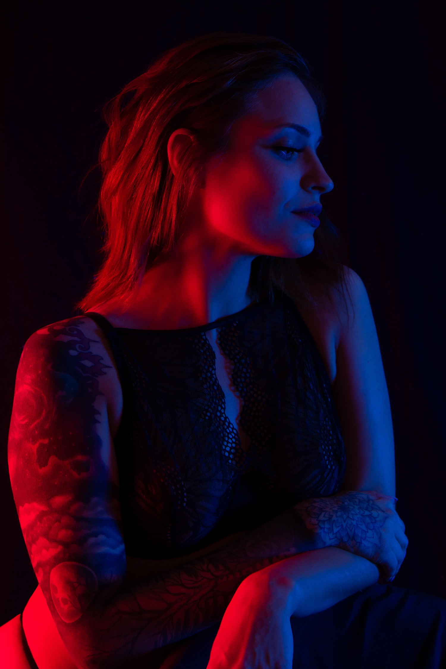 Saskatoon boudoir a woman in lingerie leans on the back of a chair, eyes closed, face looking off camera. Split lighting with red and blue light