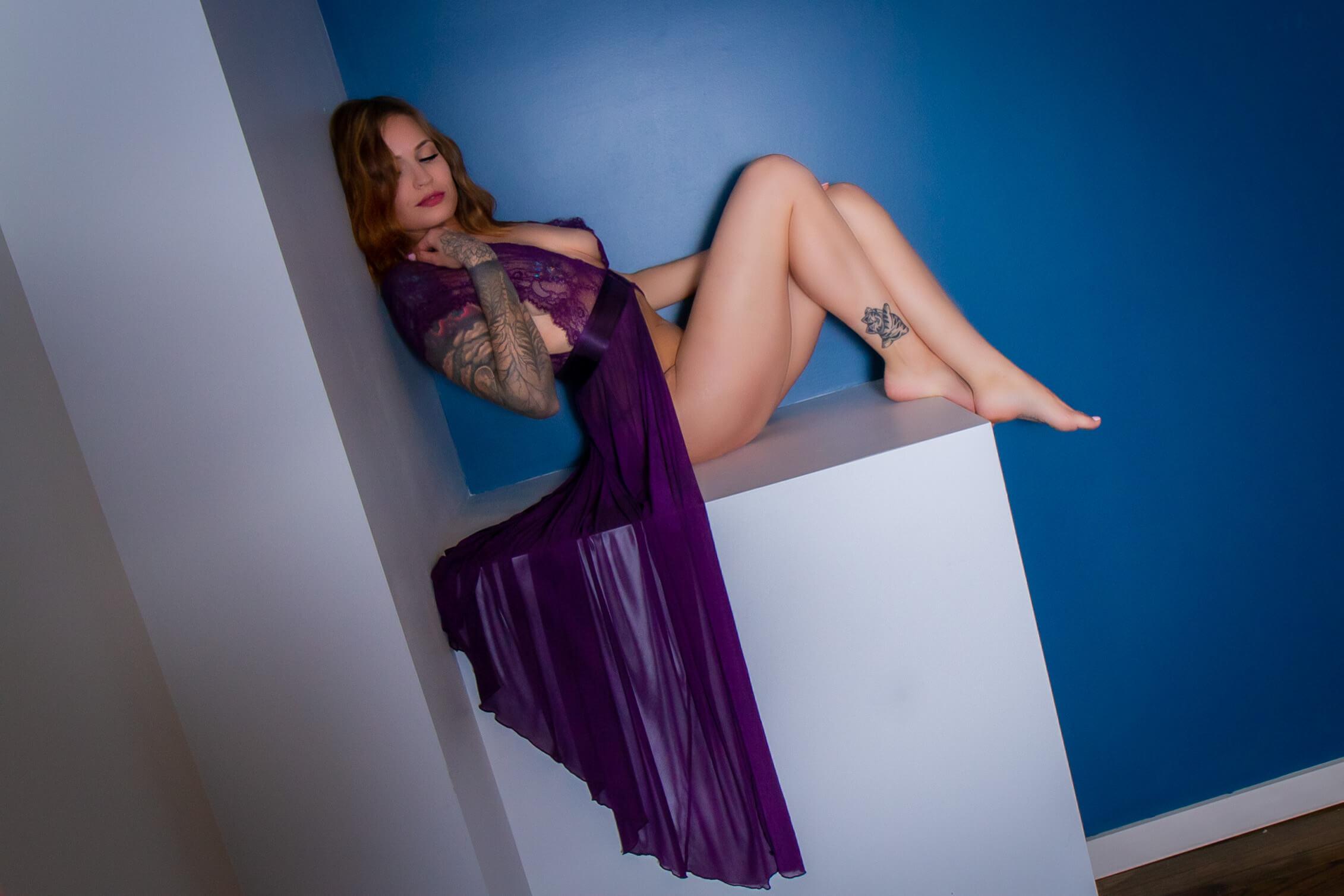 Saskatoon boudoir a woman poses on a sturdy shelf, wearing a purple robe that drapes over the edge of the shelf