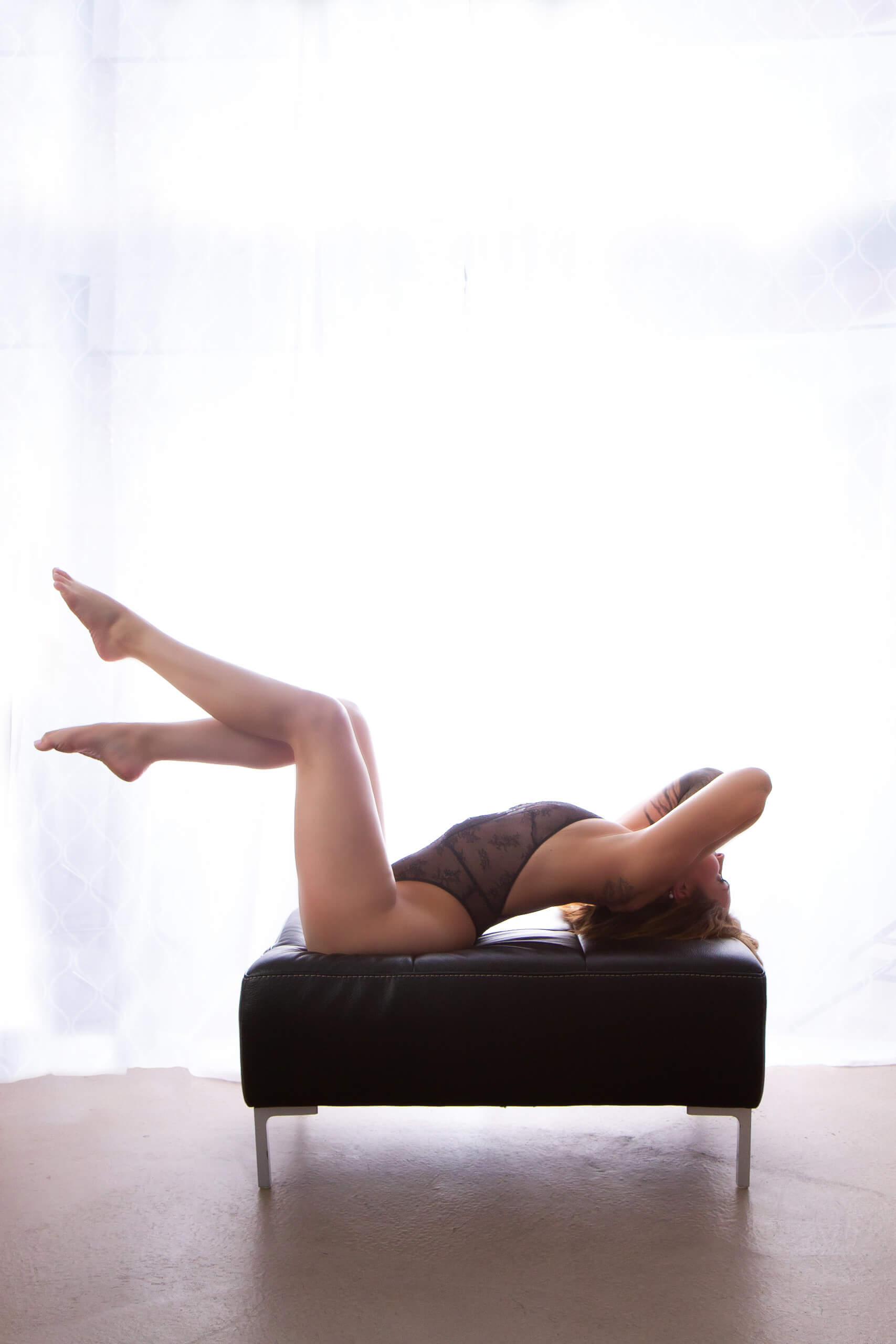 Saskatoon boudoir a woman in lingerie arches her back with her legs in the air in front of a bright white curtain